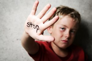 child holding hand up with word stop on his hand