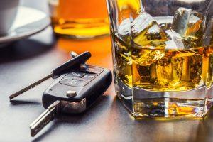 car key next to a glass of alcohol