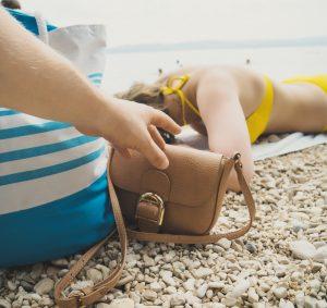 person stealing a purse at the beach