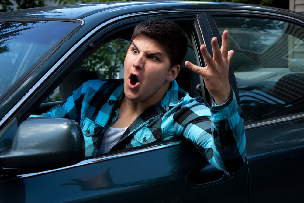 man with hand out his car window having road rage